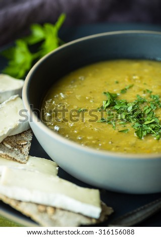 Fresh split pea soup with crackers and brie cheese - stock photo