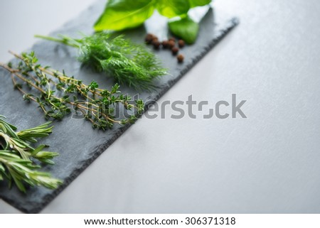 Fresh sprigs of rosemary, thyme, dill, and basil are arranged on a slate stone platter. Peppercorns are dotted among them. - stock photo