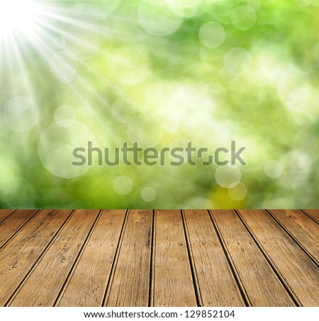 Fresh spring green bokeh background with wooden table for Your products displays.. Beauty natural background - stock photo
