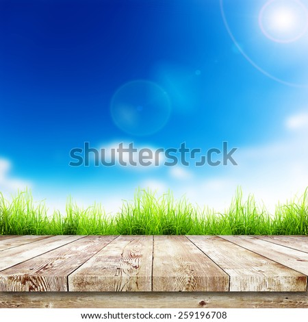 Fresh spring green grass with blue bokeh and sunlight and wood floor. Natural background - stock photo