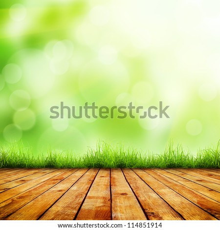 Fresh spring green grass with green bokeh and sunlight and wood floor. Beauty natural background - stock photo