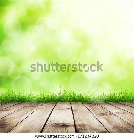 Fresh spring green grass with green bokeh and sunlight and wood floor. Natural background - stock photo