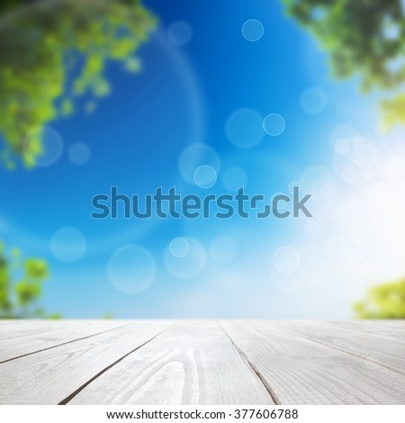 Fresh spring green leaves with blue bokeh and sunlight and wood floor. Natural background - stock photo
