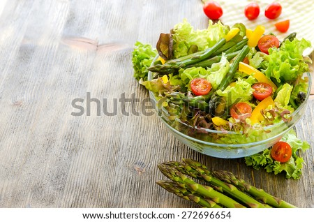 Fresh spring mixed salad with green asparagus copy space background - stock photo