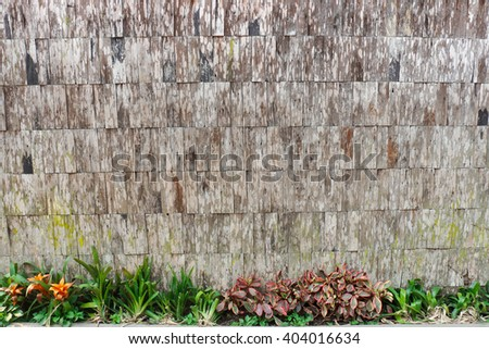 Fresh spring plant and flowers over wood fence background or texture - stock photo