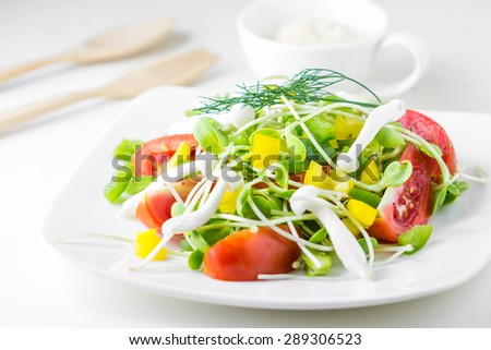 Fresh spring salad. tomatoes, yellow and green pepper,Sunflower sprouts in a bowl on a white background