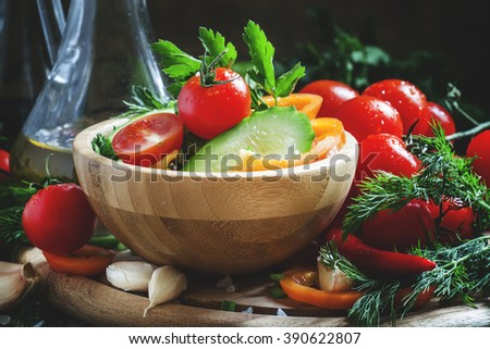 Fresh spring salad with bell pepper, tomato, cucumber, herbs and spices with olive oil, selective focus