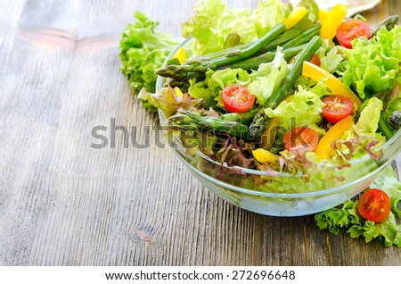 Fresh spring salad with green asparagus copy space background - stock photo
