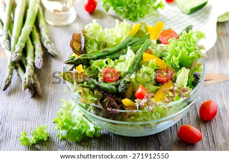 Fresh spring salad with green asparagus, small tomatoes and paprika - stock photo