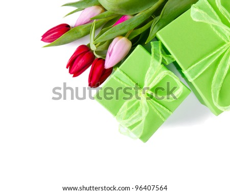 Fresh spring tulips with gifts, isolated on white background - stock photo