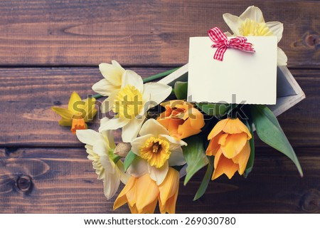Fresh  spring yellow narcissus and  tulips flowers in wooden box and empty tag  on brown  painted wooden planks. Selective focus. Place for text. Toned image. - stock photo