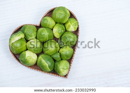 fresh sprout in heart shape on table - stock photo