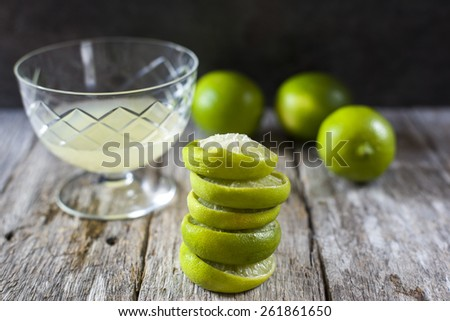 fresh squeeze of limes in clear glass and stack of rind on white - stock photo
