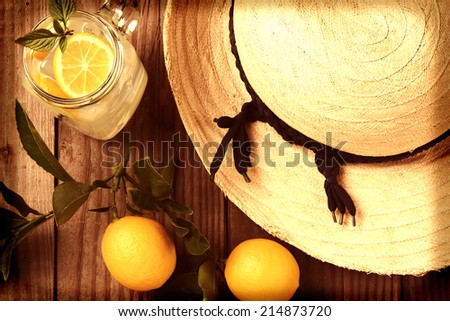 Fresh Squeezed Lemonade on a rustic wooden table with lemons and a sun hat. Horizontal format with an instagram feel, shot from a high angle, with vignette. - stock photo