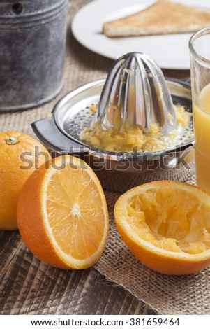 fresh squeezed orange juice for breakfast with glass and squeezer on vintage wooden table in morning light - stock photo