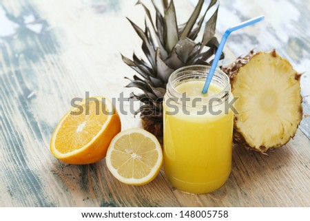 Fresh squeezed orange,lemon and pineapple juice arranged with fruits on wooden rustic table. Shot at daylight, shallow depth of field. - stock photo