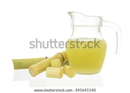 Fresh squeezed sugar cane juice in jug with cut pieces cane isolated on white background - stock photo
