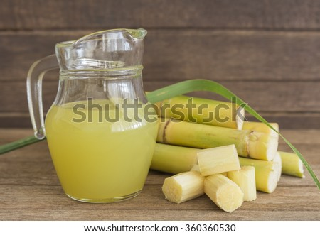 Fresh squeezed sugar cane juice in pitcher with cut pieces cane on wooden background.