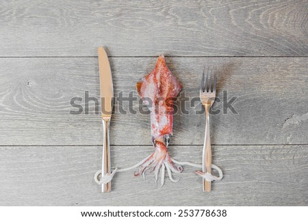 Fresh squid on wooden table holding fork and knife - stock photo