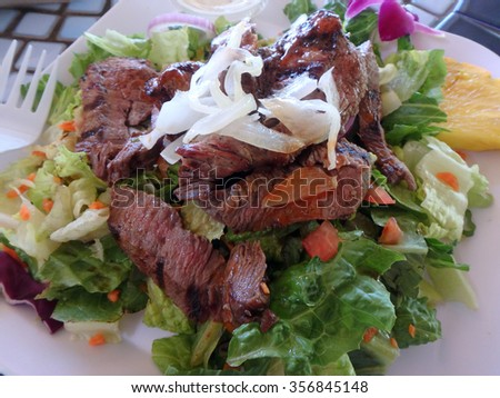 Fresh Steak Salad with lettuce, onions, carrot, tomatoes, and pineapple slice on a to go  square plate with plastic fork on a table. - stock photo