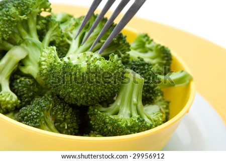 Fresh steamed broccoli florets in a bright bowl. Fork in the background. - stock photo