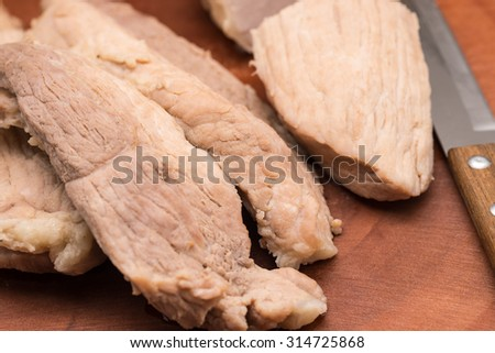 Fresh steamed or boiled pork meat with knife on wood cutting board for food preparation background  - stock photo