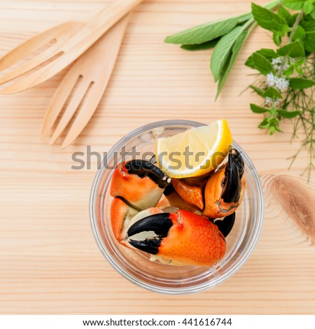 Fresh steamed red crabs leg in glass bowl . Red crabs leg with ingredients. Steamed red crabs leg with herbs Fennel ,parsley,rosemary,lemon and mint with fork on wooded background. - stock photo