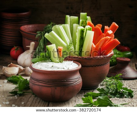 Fresh sticks carrots, celery, cucumber and white sauce with herbs and spices in a clay bowl in a rustic style, selective focus - stock photo