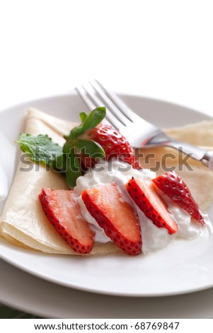 Fresh Strawberries and Cream over a Crepe against a white background