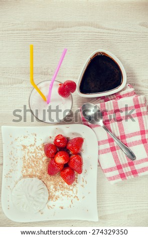 Fresh strawberries and whipped cream on a plate, fondant bitter chocolate in a bowl - stock photo