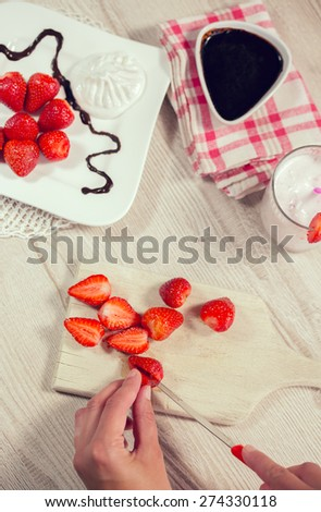 Fresh strawberries and whipped cream on a plate, fondant bitter chocolate in a bowl. Drink smoothies summer strawberry.Female hand cut strawberries - stock photo