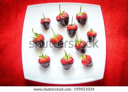 Fresh strawberries covered with dark chocolate - stock photo