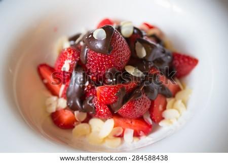 fresh strawberries dipped in dark chocolate. Shallow dof - stock photo