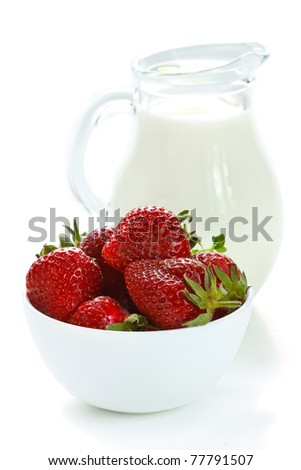 Fresh strawberries in a bowl and glass jug of milk on a white.