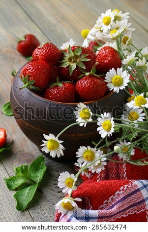 Fresh strawberries in a bowl with flowers daisies on a wooden background - stock photo
