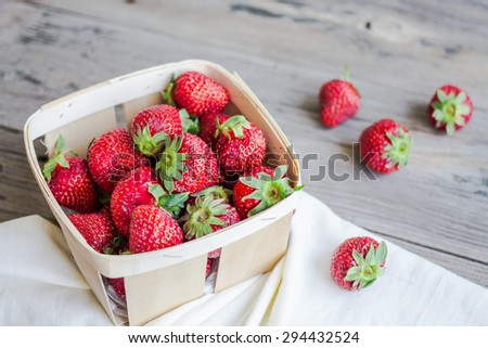 fresh strawberries in a box on a gray wooden board, rustic background, raw food, summer berries, selective focus