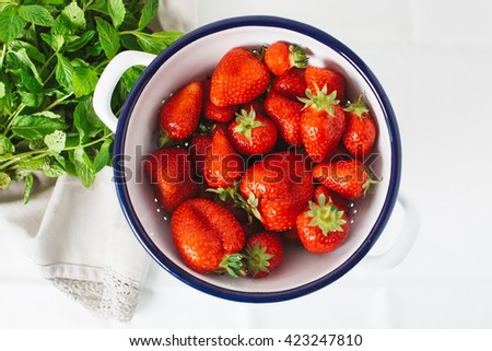 Fresh strawberries in a colander with mint herb - stock photo