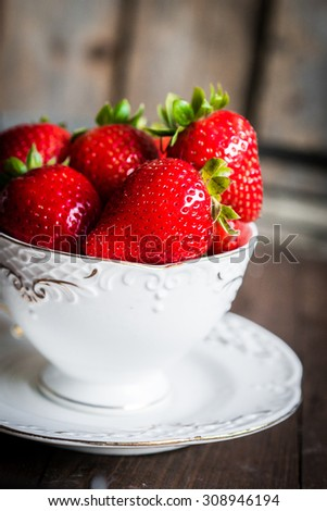 Fresh strawberries in a cup on wooden background