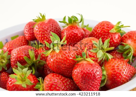 Fresh strawberries in a white bowl against white background - stock photo