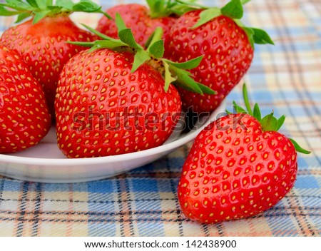 Fresh Strawberries in a White Plate on a Picnic Checkered Tablecloth - stock photo