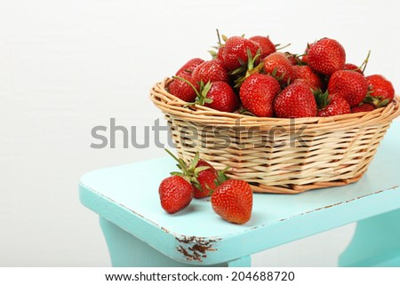 Fresh strawberries in basket on white wall background - stock photo