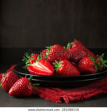 Fresh strawberries in black plate with linen napkin on dark wooden background. - stock photo