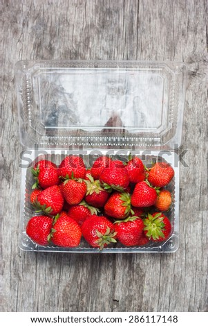 Fresh strawberries in plastic box on a background of a wooden table