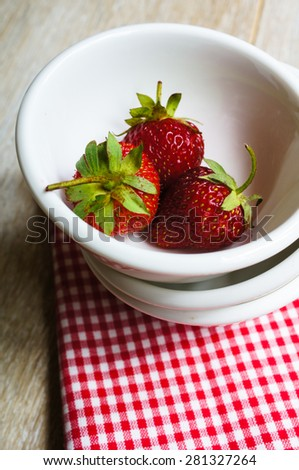 Fresh strawberries in the bowl on the old wooden background