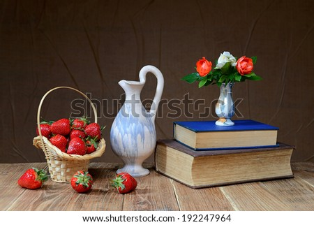 Fresh strawberries in wicker baskets and books on the table - stock photo