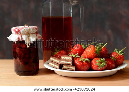 Fresh strawberries, jam, juice and chocolate on the table - stock photo