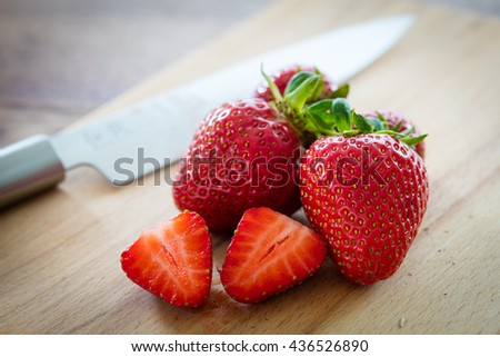 fresh strawberries on a wooden plate with a knife