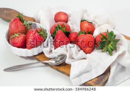 Fresh Strawberries on board cutting on striped napkin - stock photo