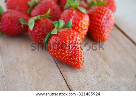 Fresh strawberries on wooden table - stock photo