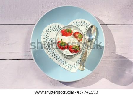 Fresh strawberries with fruit yoghurt and whipped cream on light pink wooden table